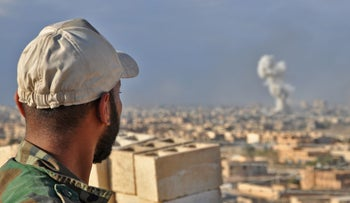File photo: A supporter of the Syrian military looks on after a regime airstrike in Deir Ezzor, July 26, 2018.