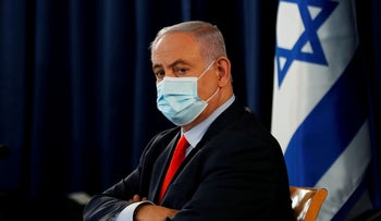Israeli Prime Minister Benjamin Netanyahu wears a mask as he looks on during the weekly cabinet meeting in Jerusalem May 31, 2020