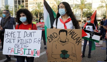 Protesters hold signs during a rally against Israel plans to annex parts of the West Bank.