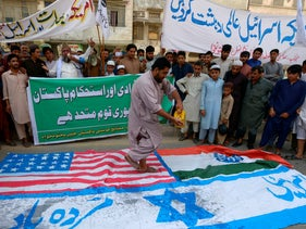 A Sunni Muslim prepares to torch flags of US, India and Israel during a rally against Israel and United States to mark the Al-Quds (Jerusalem) Day in Ramadan. Peshawar, May 22, 2020