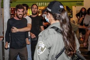 Protesters react as police moves to clear a demonstration against a planned move by Israel's government to annex parts of the West Bank, Tel Aviv, June 6, 2020.
