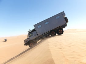 An all-terrain vehicle makes its way across sand dunes in Africa on a trip with Overland Travel.
