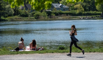 A woman jogs past sunbathers in Stockholm, Sweden May, 2020. Headlines declared that the Swedes admit that their model for dealing with COVID-19 has collapsed. They were incorrect.