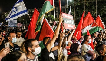 Palestinian Liberation Organization and Israeli flags held at a protest against annexation of parts of the weest Bank, Tel Aviv, June 6, 2020