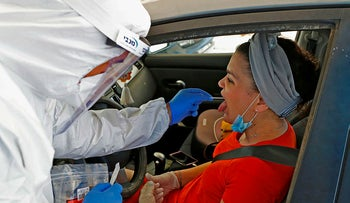 Israeli medical personnel take samples at a drive through COVID-19 testing facility in Ramat Hasharon in the suburbs of Tel Aviv, on June 1, 2020.
