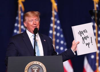 "President Donald Trump speaking at a pro-Trump rally organized by U.S. evangelicals, January 2020.He is holding up a sign that states ""Never give up."""
