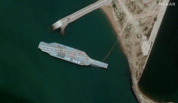 In this Sunday, June 7, 2020 satellite photo provided by Maxar Technologies, a fake aircraft carrier is seen off the coast of Bandar Abbas, Iran