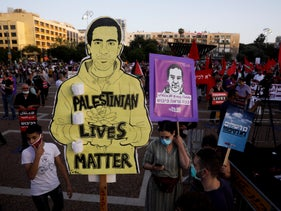 Protesters hold placards bearing the image of Eyad Hallaq, a Palestinian with severe autism who was killed recently by police officers in Jerusalem, in Tel Aviv, on Saturday, June 6, 2020.