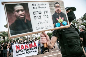 A protester in Tel Aviv holds a sign featuring George Floyd and Eyad Hallaq, an unarmed Palestinian shot dead by Israeli border police, June 6, 2020.