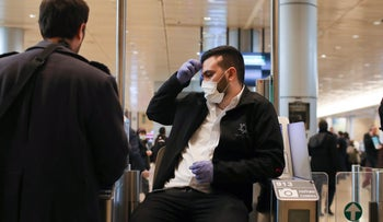 Security personnel wears a face mask at Israe's Ben Gurion Airport as passengers go through security.