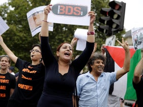 A protester holds a placard reading 'BDS' during a gathering on the sidelines of an event celebrating Tel Aviv, in central Paris, August 13, 2015.