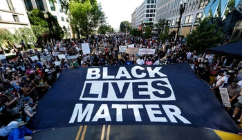 Demonstrators hold a giant sign at the Black Lives Matter Plaza, near the White House, during a protest against racial inequality, Washington, June 6, 2020.