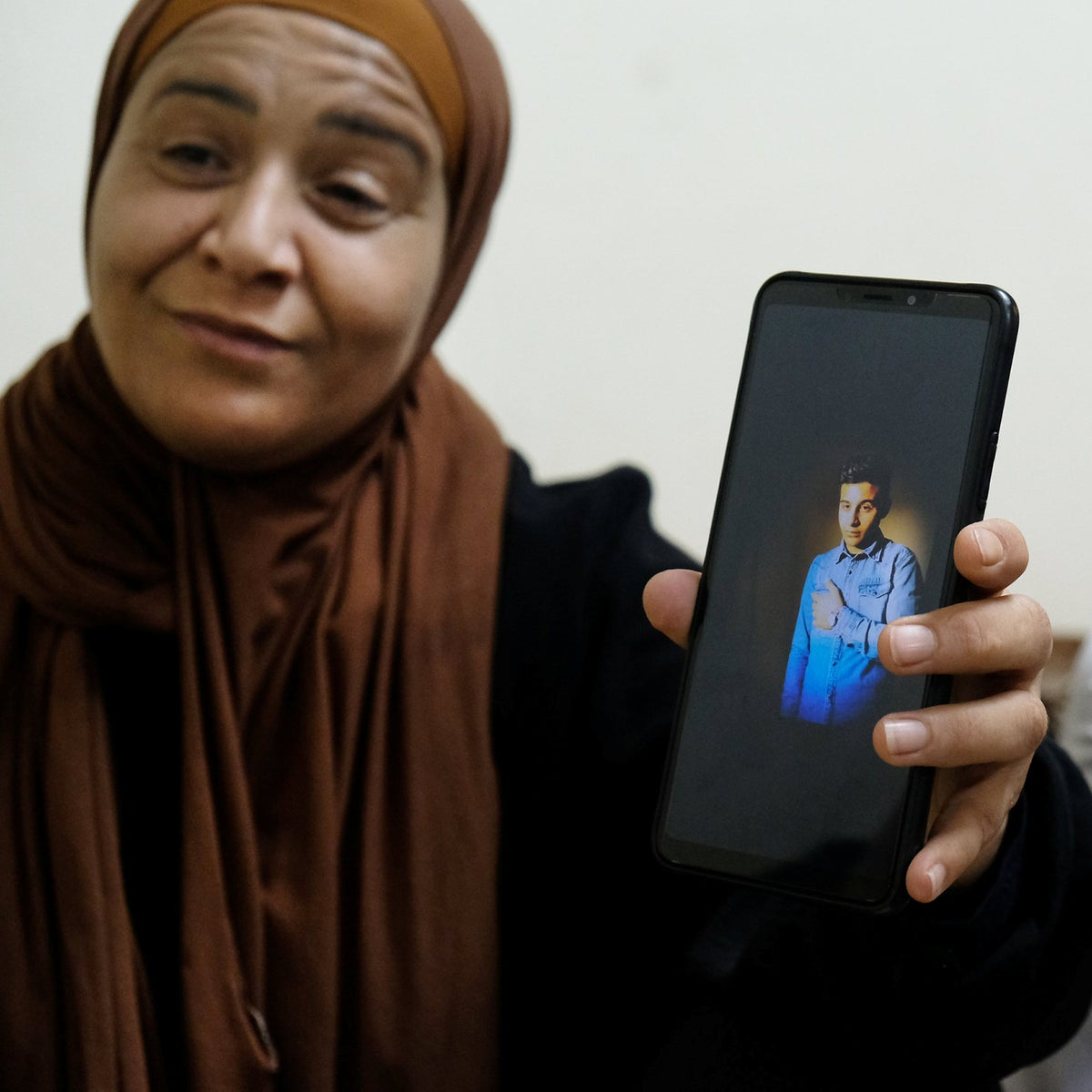 Zeid Qaysiyah's mother Barlanet shows a photo of her deceased son on her cell phone. Her other son, Jihad, sits next to her.