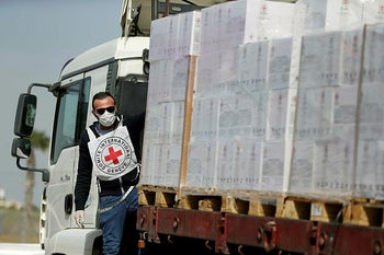 A Palestinian worker rides on a truck carrying medical equipment donated by the International Committee of the Red Cross (ICRC) at Kerem Shalom crossing in the southern Gaza Strip April 21, 2020.