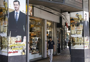 A man walks past window shops while nearby pillars are adorned with posters showing Syrian President Bashar al-Assad in Damascus, on June 10, 2020.