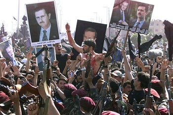 Syrian presidential guards, waving pictures of President Hafez al-Assad and his son Bashar, pay their last respects to their late president in Damascus, on June 13, 2000.