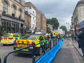 Police cars are seen at a cordon in place on Stoke Newington High street in London, U.K., June 12, 2020.