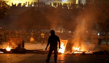 A member of the Lebanese riot police walks near burning fire during a protest against the fall in pound currency and mounting economic hardship, in Beirut, Lebanon June 12, 2020.