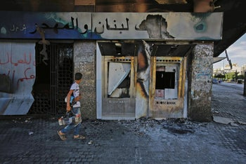 A youth walks past a burnt down branch of a Lebanese bank after it was set on fire and vandalized by protesters earlier, in al-Nour Square in Tripoli, June 12, 2020.