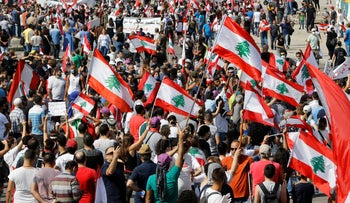 Anti-government protesters hold Lebanese national flags as shout slogans during a protest in downtown Beirut, June 6, 2020.