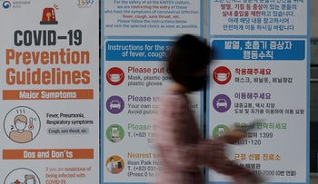 A woman wearing a face mask walks near a banner showing precautions against the new coronavirus at an exhibition and convention center in Goyang, South Korea, Friday, June 12, 2020