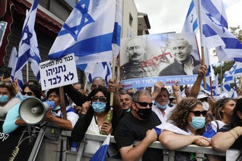 Netanyahu supporters hold flags and a poster depicting Prime Minister Benjamin Netanyahu's criminal trial as analogous to that of French officer Alfred Dreyfus, unjustly convicted of treason in 1895. Jerusalem, May 24, 2020