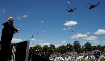 President Donald Trump applauds as Army helicopters fly overand West Point cadets toss their caps into the air at the end of commencement ceremonies on the parade field, at the United States Military Academy in West Point, N.Y., Saturday, June 13, 2020