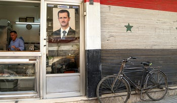 A picture of Syrian President Bashar Assad is seen on a door of a butcher shop  in Damascus, Syria, April 22, 2020.