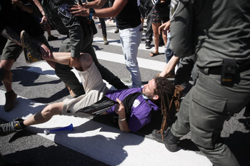"""A protester is dragged away by police officers during a """"demonstration of fury"""" protest, Jerusalem, June 15, 2020."""