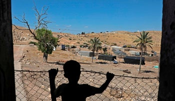 A Palestinian child stands at his family land east of Tubas, near the Jordan Valley, June 15, 2020. -