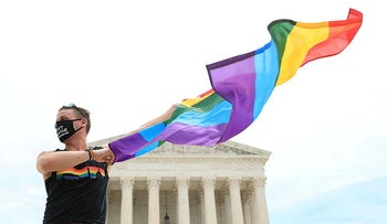 Joseph Fons holding a Pride Flag in front of the U.S. Supreme Court building in Washington, D.C., U.S., June 15, 2020.