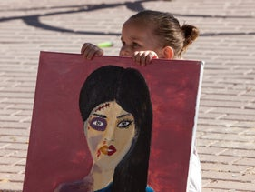 A young girl holds a painting of a battered woman at the protest against gendered violence, Rahat, June 15, 2020.