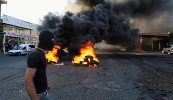 A man walks near burning tires during a sit-in protest against the fall in pound currency and mounting economic hardship, in Ghazieh, south of Lebanon, Lebanon June 12, 2020.