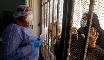 A woman who is in a contact with people with coronavirus receives free medicines provided by the ministry of health, at a medical centre in Cairo, Egypt, June 3, 2020.