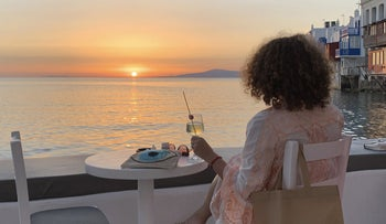 A visitor watching the sunset at a bar on the island of Mykonos, Greece, June 9, 2020.
