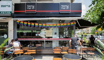 A rainbow flag banner hangs in front of Aroma Cafe in Tel Aviv during Pride month, 2018.