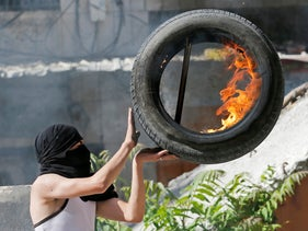 A Palestinian holds a burning tire during a protest against Israel's plan to annex parts of the West Bank, in Hebron June 12, 2020.