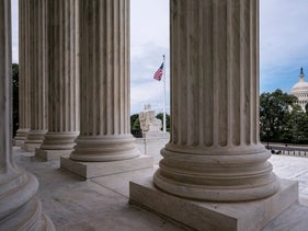 In this June 15, 2020, file photo the columns of the Supreme Court are seen with the Capitol at right, in Washington
