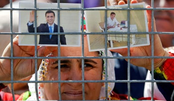 A woman holds pictures of jailed former leader of Turkey's main pro-Kurdish Peoples' Democratic Party Selahattin Demirtas in Istanbul, Turkey March 24, 2019.