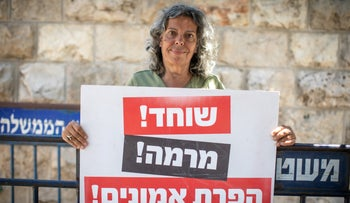 """A protester outside the Prime Minister's Residence in Jerusalem holds up a sign reading """"Bribery! Fraud! Breach of trust!"""", June 16, 2020."""