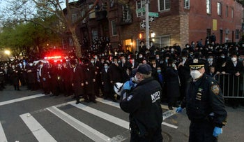 Police instruct a crowd as hundreds of mourners gather in the Brooklyn borough of New York to observe a funeral for Rabbi Chaim Mertz, April 28, 2020.