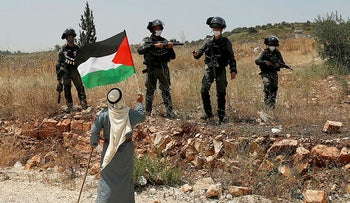 A demonstrator holds a Palestinian flag in front of Israeli forces during a protest against Israel's plan to annex parts of the occupied West Bank, near Tulkarm June 5, 2020.