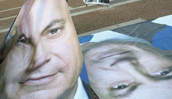 People bring posters of Prime Minister Benjamin Netanyahu prior to an election rally in Tel Aviv, Israel, March 15, 2015.