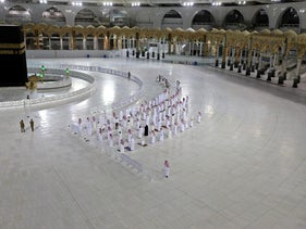 Worshippers perform Isha prayer while keeping distance between them next to the Kaaba in Mecca's Grand Mosque, Islam's holiest site, on April 27, 2020.