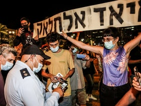 Demonstrators holding up a banner bearing Eyad Hallaq's name at a protest against Israel's annexation plan, in Tel Aviv, June 6, 2020