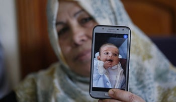 The grandmother of Omar Yagi displays a picture of him in Gaza City, June 22, 2020.