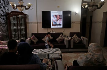 The family of Omar Yagi look at a TV screen displaying pictures of him in Gaza City, June 22, 2020.
