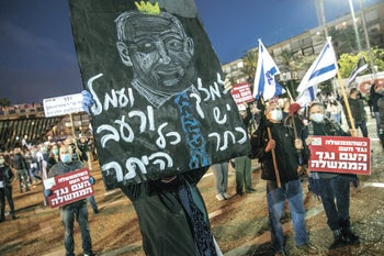Israelis hold signs depicting Netanyahu at a 'black flag' protest in Tel Aviv, April 25, 2020.