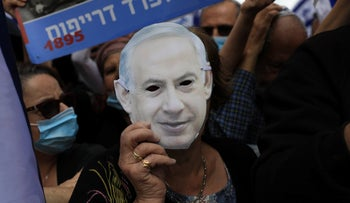 A woman holds a mask of Netanyahu's face at a rally in support of the premier ahead of the first day of his corruption trial, May 24, 2020.