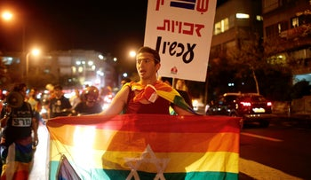 "Members of Israel's LGBT community hold pride flags and signs reading ""Equal rights now!"" in Tel Aviv, January 4, 2019."
